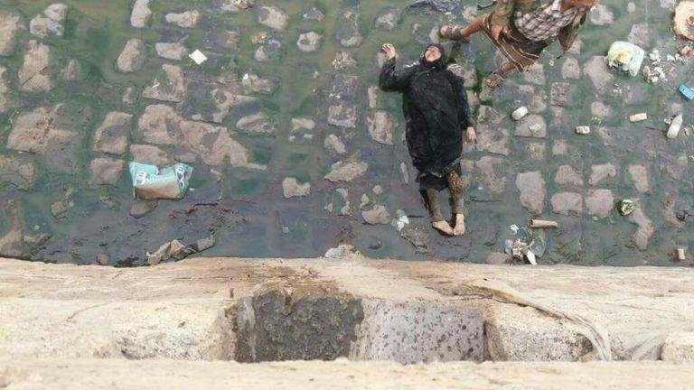 بالصورة: مرتزقة العدوان يقتلون مديرة مدرسة ويرمون جثتها من فوق أحد الجسور بتعز